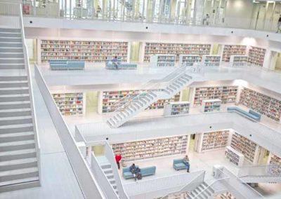 Literaturhinweis Reinkarnation, das Bild zeigt den Einblick in eine fünfstöckige weiss gestaltete Bilbliothek, deren Treppen in einem offenen quadratischen Innenraum von Etage nach Etage nach oben führen. Die Bücherregale befinden sich an den Wänden der umlaufenden Galerien.